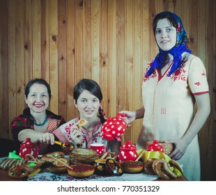 Women in traditional  clothes eating pancake with tea during  Shrovetide