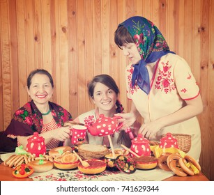 Women in traditional  clothes eats pancake with tea during  Shrovetide