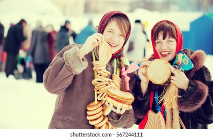 Women in traditional  clothes tasting pancake  during  Shrovetide