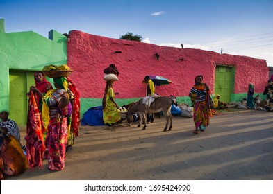 Women in traditional costumes with baskets on their heads at the colourful street market in the city of Harar. Harar, Ethiopia. 24 August 2014