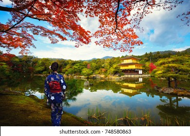 Women in traditional japanese kimonos looking at Kinkakuji Temple in Kyoto Japan