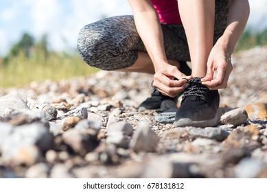 women trail running workout outdoor wait tying shoelaces