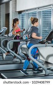women training on treadmills at gym