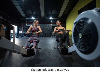 Women training rowing in gym with exercises machines and pull rope