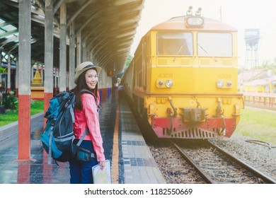 Women travel with luggage at the train station. The concept of active lifestyle and happy travel.