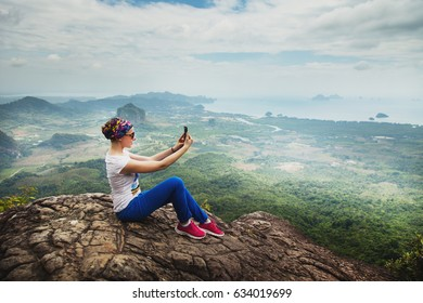 Women travel sit on a cliff on a rich forest mountain. Tab Kak Hang Nak Hill Nature Trail. Do selfie
