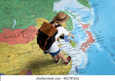 Women traveler Is planning a tour her standing on the world map.she points to Japan