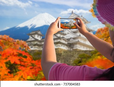 A women traveler use mobile phone take a photo landscape during autumn season with Himeji castles and mountain Fuji background. One of Japan's premier historic castles, Japan