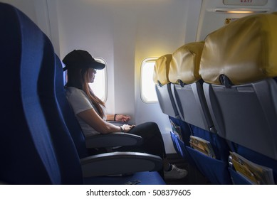 Women traveling by an airplane. Woman travel  sitting by aircraft inside window and looking outside.