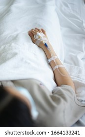Women treatment in patient bed with IV tube, Grain with hands focus