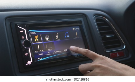 a women turn off her audio system in her car 23d1b33445