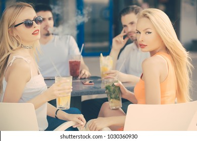 Women twins and men friends relax in cafe outdoor. Man vapor hookah pipe in shisha bar lounge. Celebration, party, proposal, birthday. Bad habits, party, addiction.