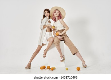 women two friends sit on a cube of oranges on the floor