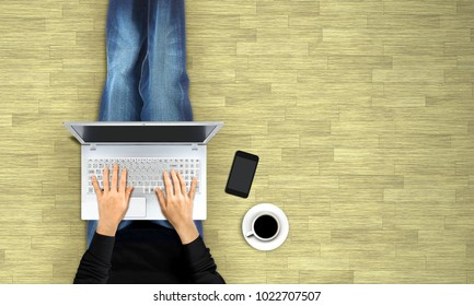 Women typing laptop on wodden floor from top view
