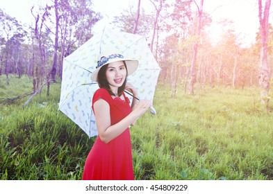 Women with umbrella at wheat field. Photo in old retro style.Fashion portrait of a beautiful young woman in autumn forest.