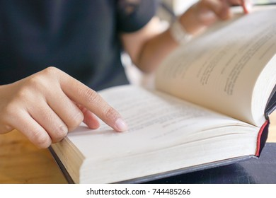 women use finger help to read book. book lover concept.