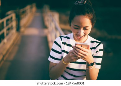 women use mobile phone at outdoor countryside with sunset light by smile happy look reading good news
