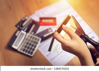 women use scissors to cut credit cards in hand with many credit card and statement on table for background