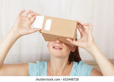 Women using cardboard VR glasses. Virtual reality.