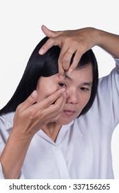 Women using contact lenses.
