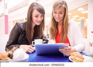 Women using digital tablet while having coffee and snacks in mall