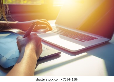 women using laptop and graphic tablet at is workspace , digital nomad , with sun effect .