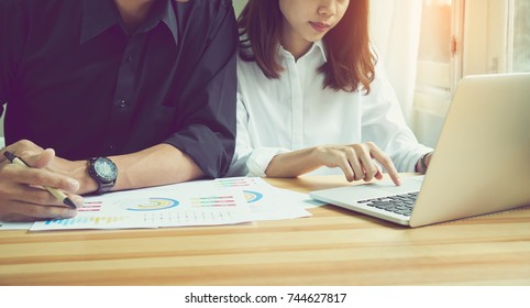 women are using the laptop on the table in the office, where men sit together is using the idea of work. Use graphics to advertise your computer screen.