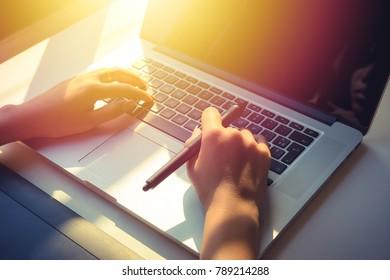 women using laptop to work , sun effect