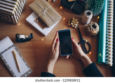 Women using mobile phone at gift wrapping table