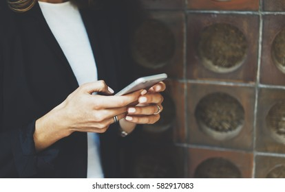 Women using smart hone isolated, hipster manager holding mobile gadget, girl text message, connect concept, blur background brick mock up, female hands touch digital screen, user social network
