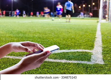 Women are using smart phone on the football field .