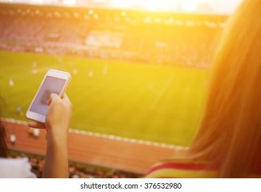 Women are using smart phone on the soccer stadium.