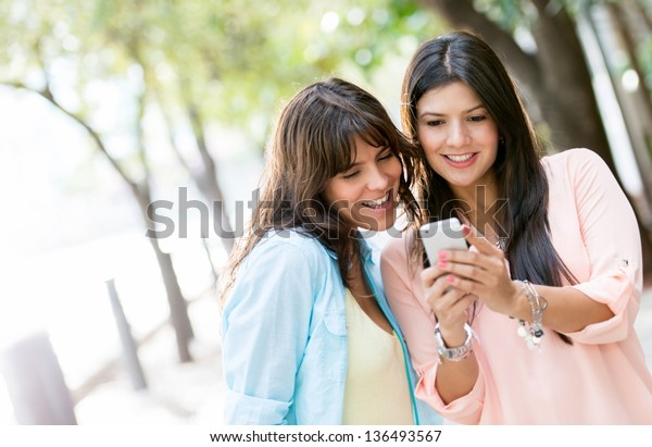 Women using a smart phone outdoors looking very happy