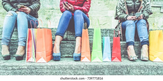 Women using smartphone for online shopping - Trendy girls sitting on stairs with high heels surfing on web with mobile phones - Winter sales and web buyers concept- Main focus on bags