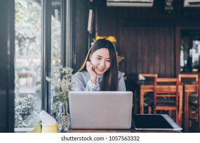 A women using tablet or mobile device on table at garden. She hand taking device and eye see on screen. She sitting in table in the garden and she playing social network.