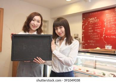 women with waitress uniform holding a blackboard