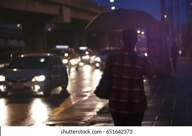 Women walk alone with blur background raining.