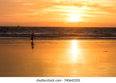 the women walk on the beach at the sunset time
