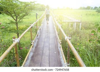 Women walk on wooden bridge, flower garden
