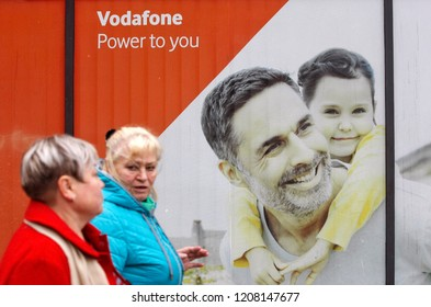 Women walk past of Vodafone advertising banner in Kiev, Ukraine, on 20 October 2018