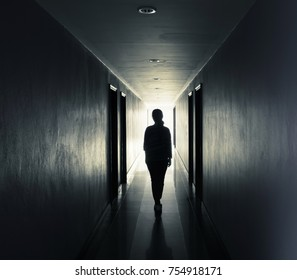 Women are walking alone in the dark.Light at the end of the tunnel concept