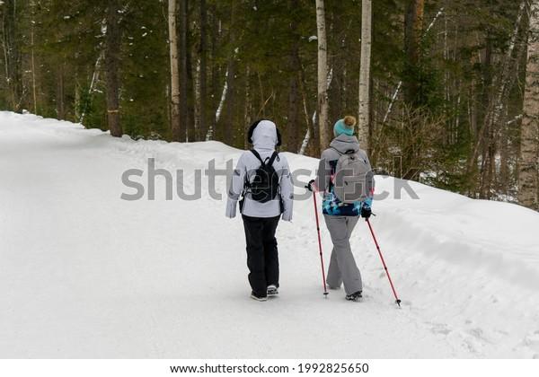 women-walking-along-winter-road-600w-199