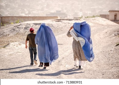 Women walking in a blue burka on a dirt road with a juvenile with a dress showing in Kabul Afghanistan