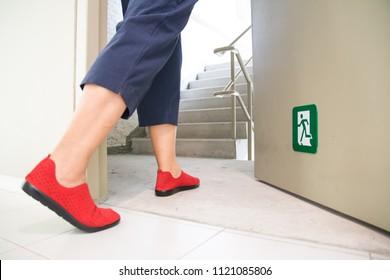 women walking to the emergency fire exit door