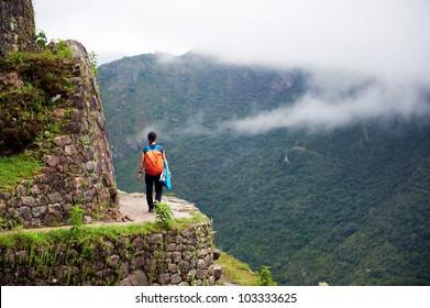 Women walking on the edge of a cliff, Machu Picchu, Peru