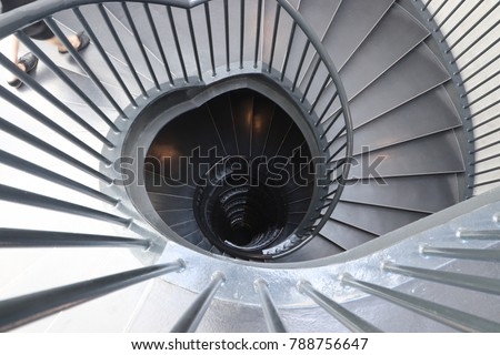 A Women Walking Swiftly Down A Spiral Staircase. This Image Can Be Used To  Represent