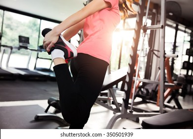 Women warm up before a workout in the gym.