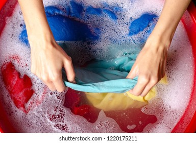 Women washing color clothes in basin enemale powdered detergent, top view