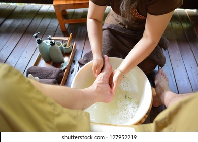 The women is washing his foot to prepare for thai spa foot massage