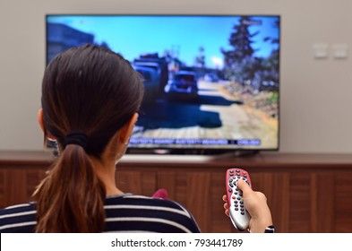 Women watching news on tv and use remote controller